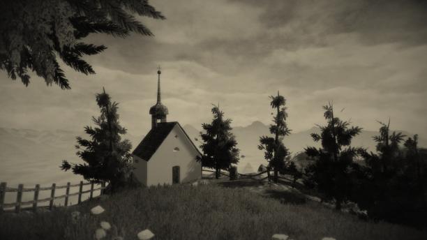 Kapelle von Mundaun vor einem Abgrund, der mit einem hölzernen Zaun gesichert ist. Rechts neben der Kapelle stehen einige Bäume, links einer. Im Hintergrund sind Berge und ein wolkiger Himmel zu sehen.
