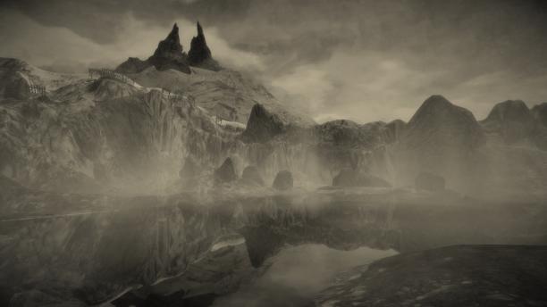 Berglandschaft mit See. Im Hintergrund Berg Mundaun mit zwei spitzen. Nebel liegt über dem See; rundherum Felsen.